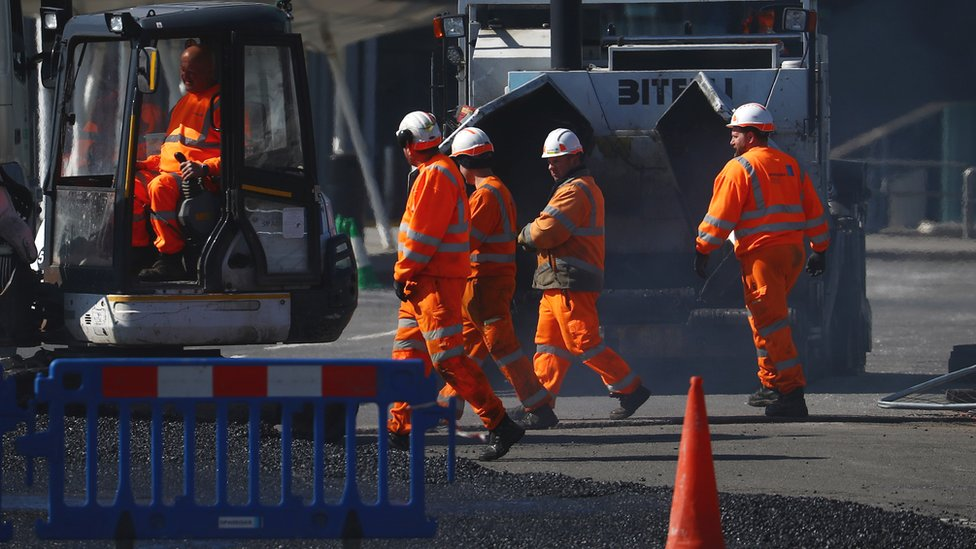 Construction workers work near the Excel Centre, London