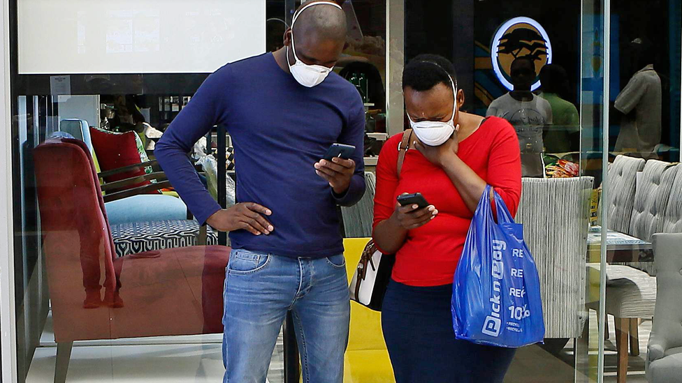 A couple wearing masks looking at their mobile phones in Pretoria, South Africa - 29 March 2020