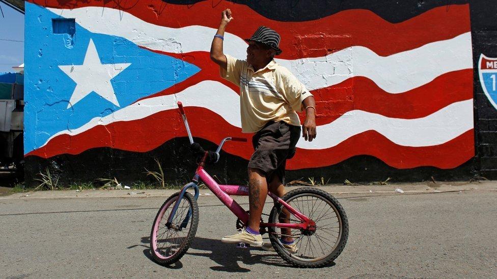 Hombre en frente de una pintura de la bandera de Puerto Rico.