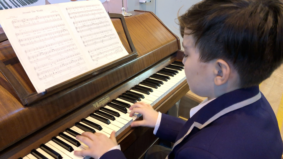 Child refugee pianist plays in charity shop