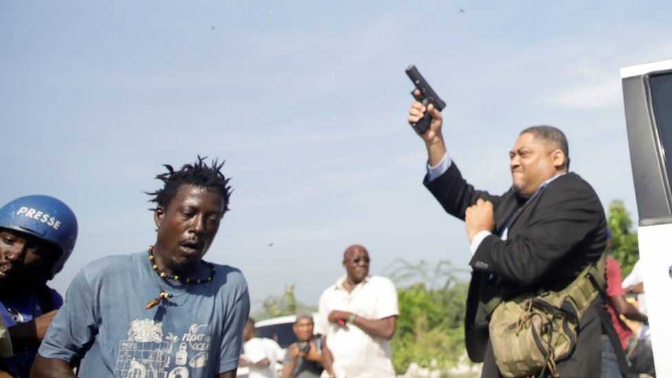 Senator Jean Marie Ralph Féthière holds a gun in the country's capital, Port-au-Prince