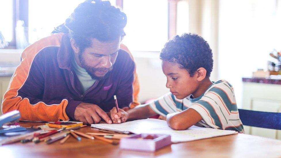 Padre haciendo deberes con su hijo.