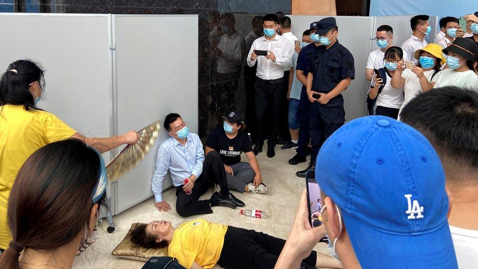 恆大財富執行董事兼總經理杜亮(中)癱坐在一位暈倒的女士旁邊(13/9/2021)