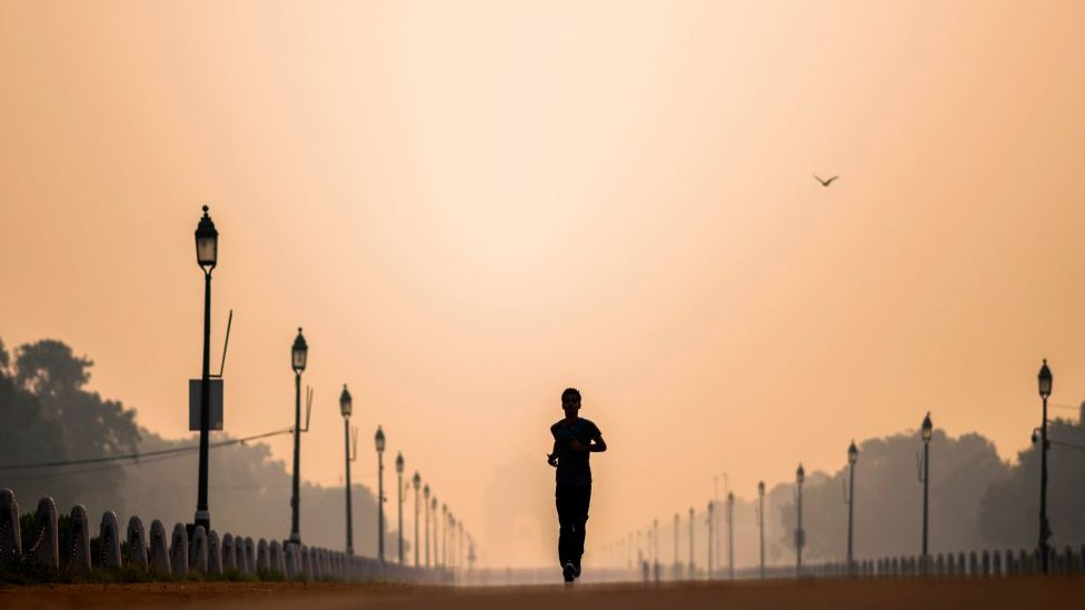 A man jogs along Rajpath street during a smoggy morning in New Delhi on October 15, 2020