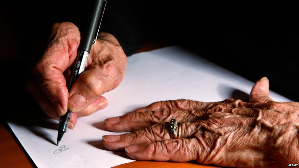 Elderly woman writing document