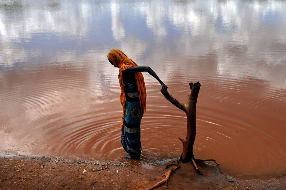 Villagers fetch water from a polluted water hole in the village of Damba in northern Kenya, 2006