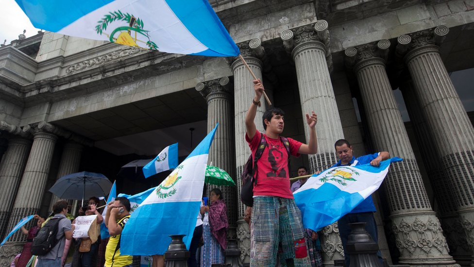Guatemalans wave national flags as they celebrate the resignation of President Otto Perez Molina, in Guatemala City, Thursday, Sept. 3, 2015