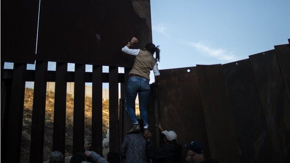 Migrantes centroamericanos saltan la valla de metal que separa la frontera el pasado 2 de diciembre.