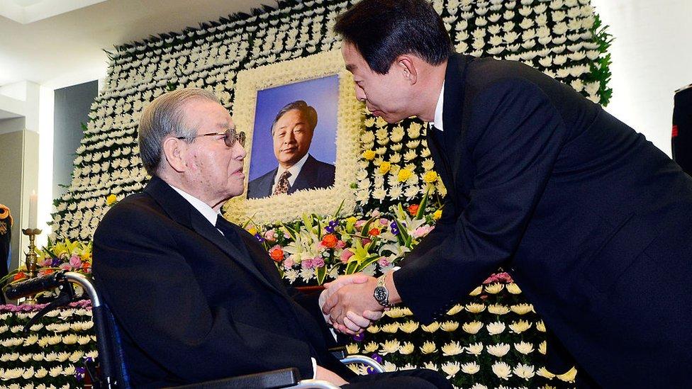 Kim Jong-Pil (L) consoles Kim Hyun-Chul (R), son of the late former South Korean president Kim Young-Sam, at a memorial altar