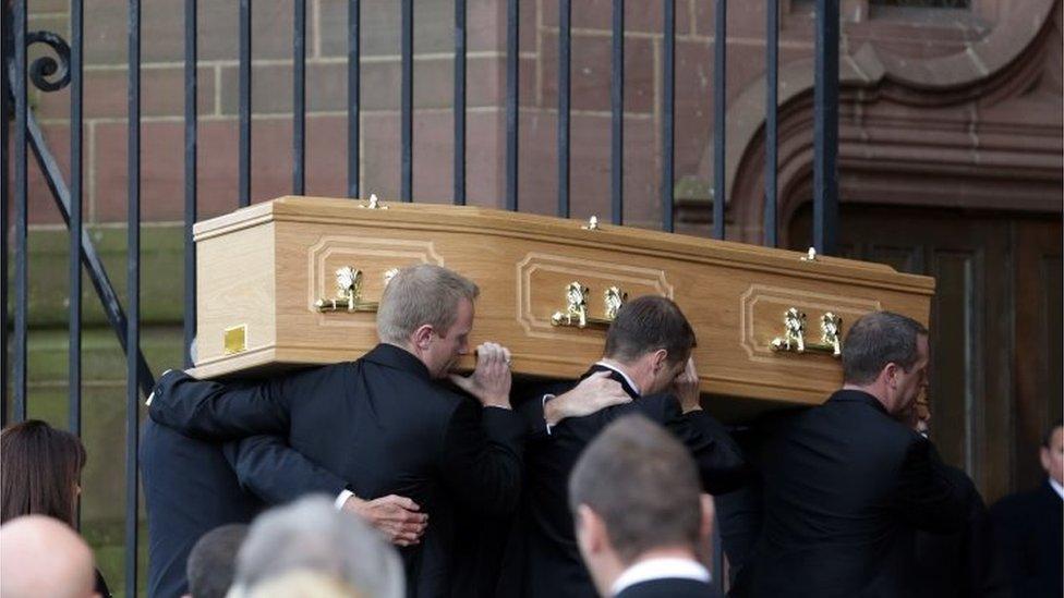 Pallbearers carry coffin in