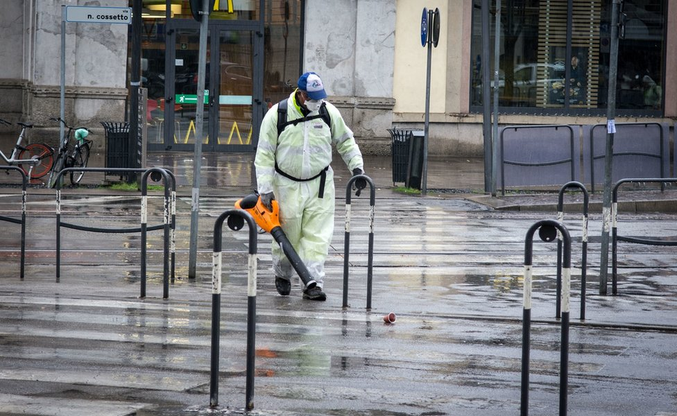 A man in overalls and sanitary equipment works in a street