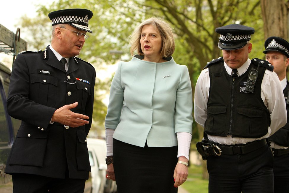 Theresa May with two police officers