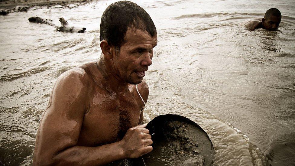 Arenero sacando arena del río.