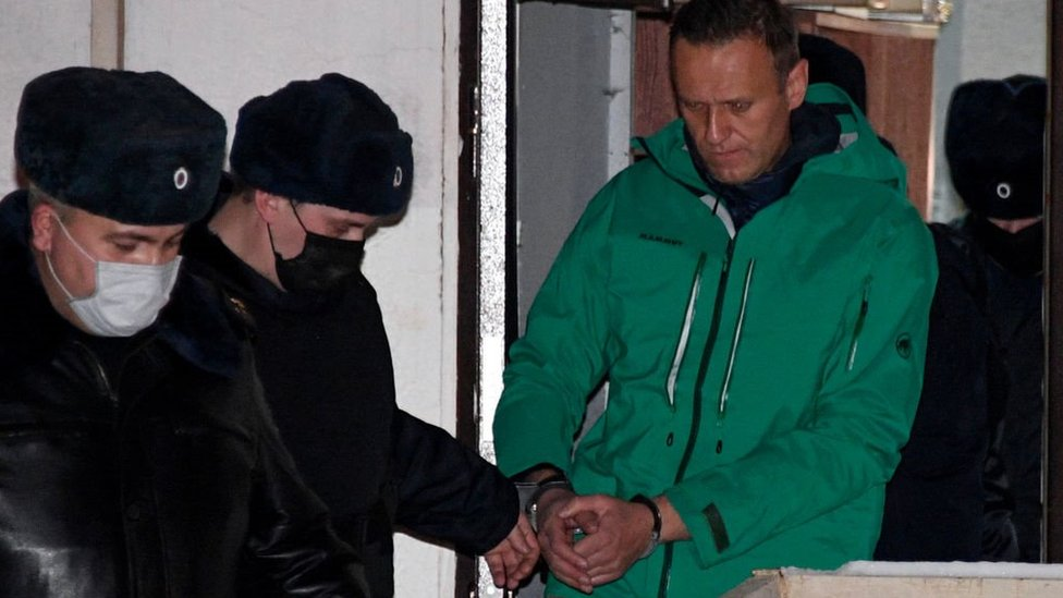 Opposition leader Alexei Navalny is escorted out of a police station on January 18, 2021, in Khimki, outside Moscow