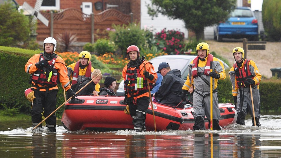 Residents are taken to safety in an inflatable boat by rescue workers in Wainfleet