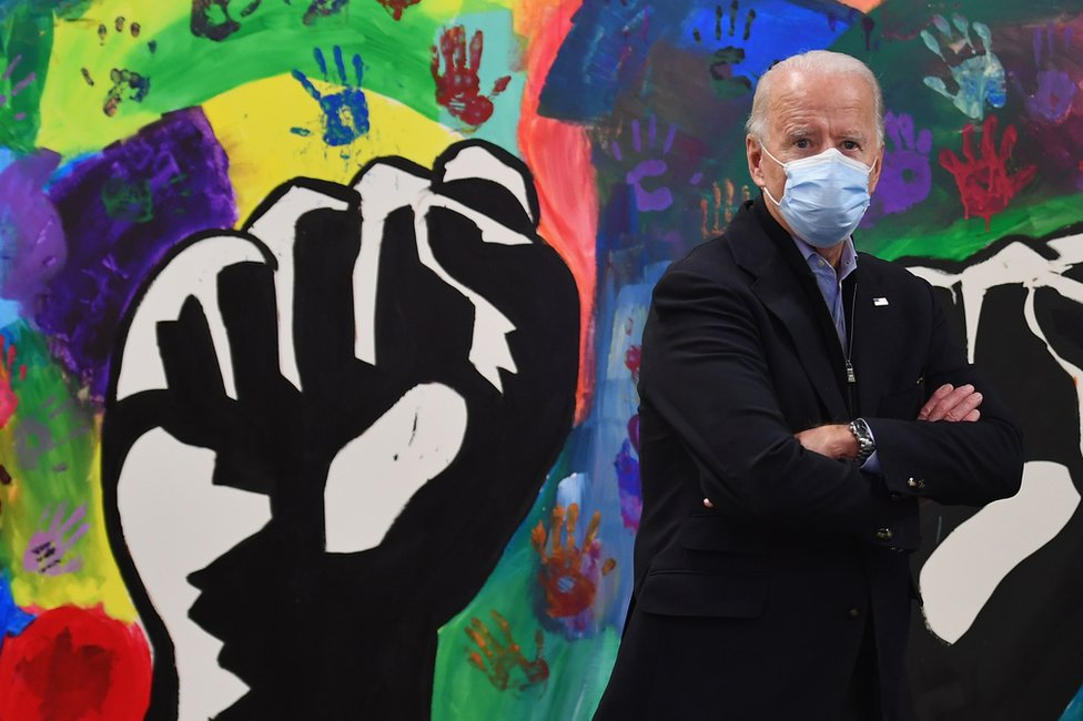Joe Biden in front of a colourful wall mural