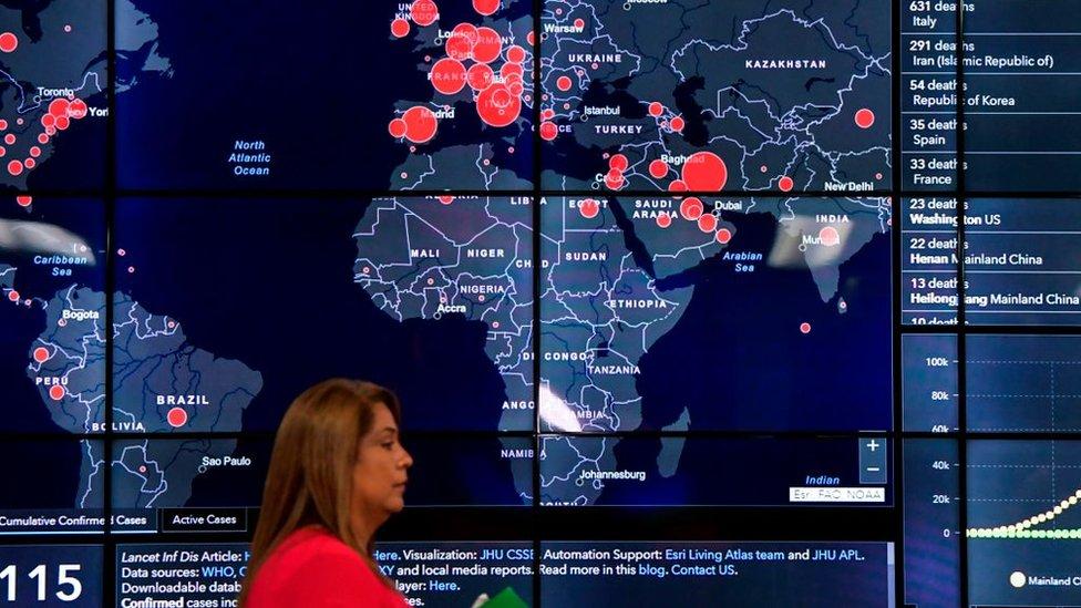 Mujer pasa caminando frente al mapa de los casos de coronavirus en el mundo.