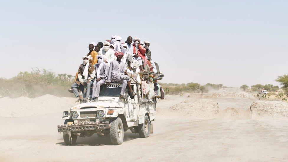 Migrantes en una camioneta en el desierto.