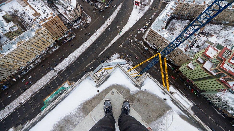 Kirill Vselensky standing on the corner of a high building
