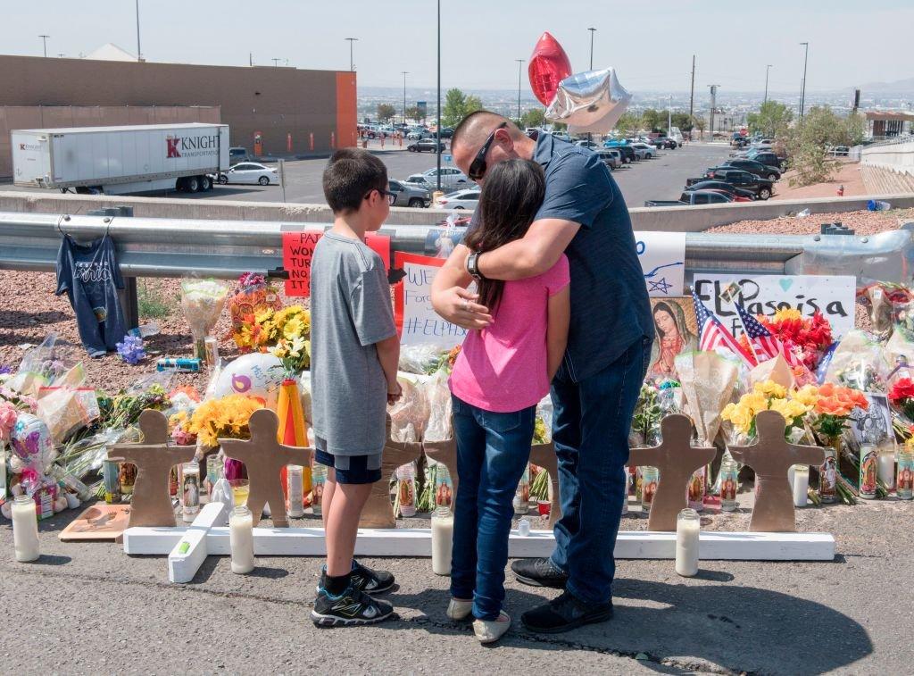 Un hombre y dos niños ante un altar por las víctimas de El Paso
