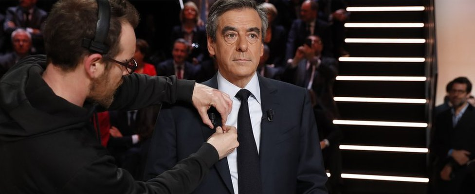 Francois Fillon (C) gets a microphone attached to his collar prior to the start of a debate of candidates organised by French private TV channel TF1 (20 March)