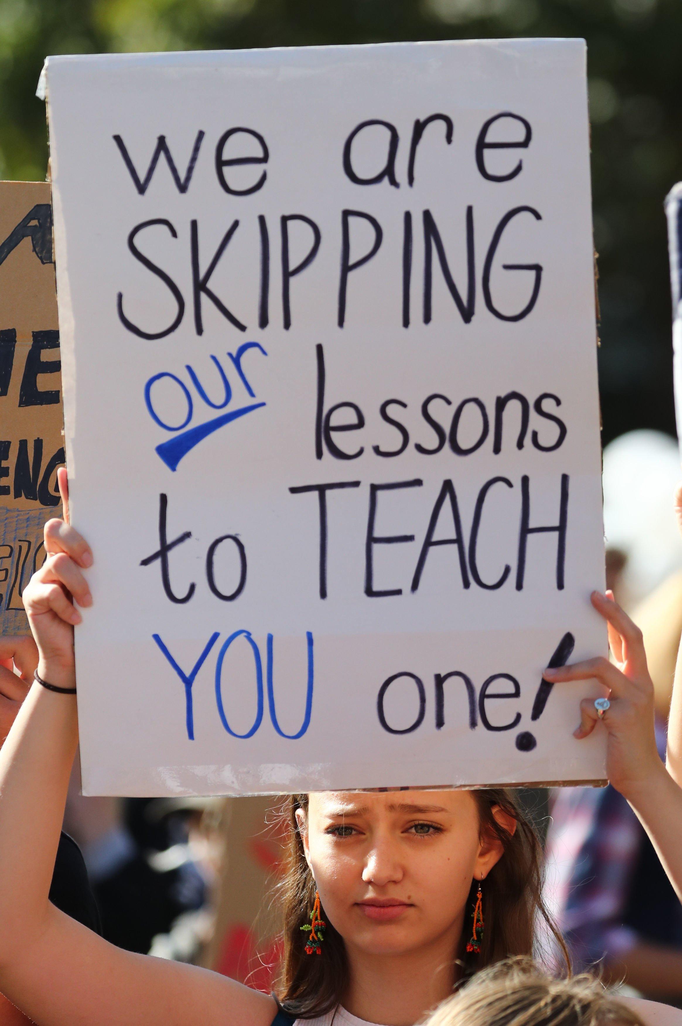 """Manifestante con una pancarta que dice: """"Faltamos a nuestras clases para enseñarte una lección"""""""