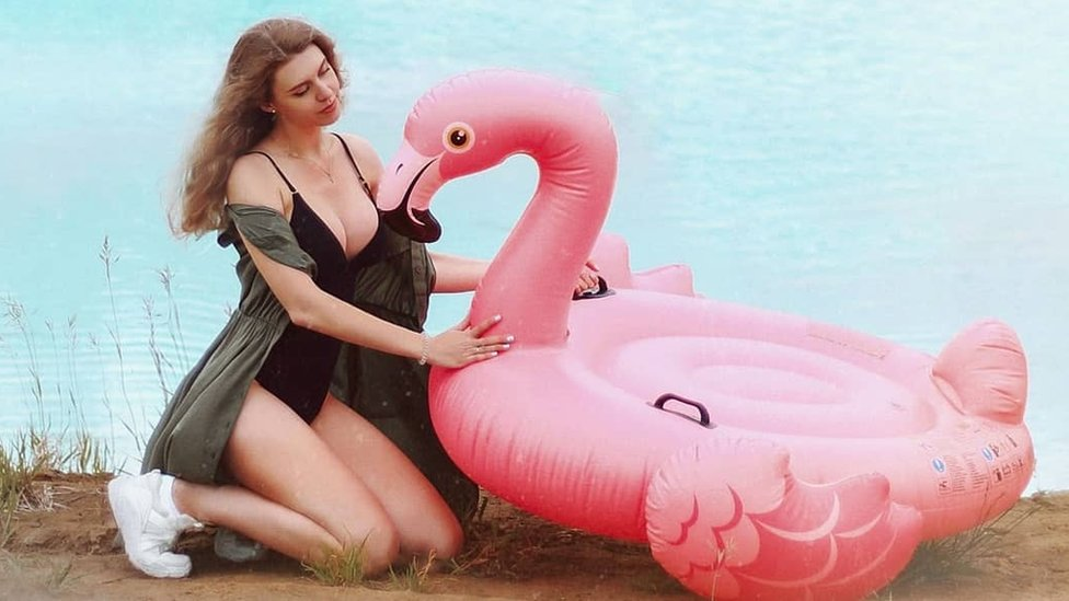 Instagram user poses by the lake with an inflatable flamingo