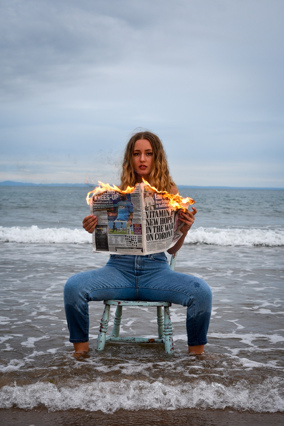 A woman, sits on the beach with water at her feet as she holds a burning newspaper
