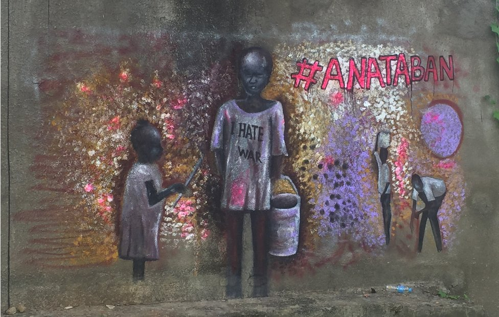 "Child carrying a bucket wearing a t-shirt saying ""I hate war"""