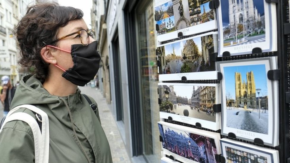 A woman looks at postcards of Brussels in a shop window