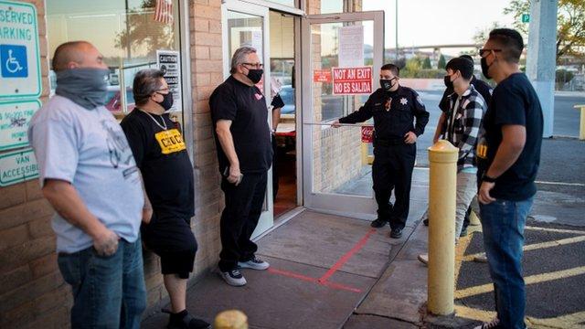Varias personas con mascarilla a las afueras de un local en El Paso