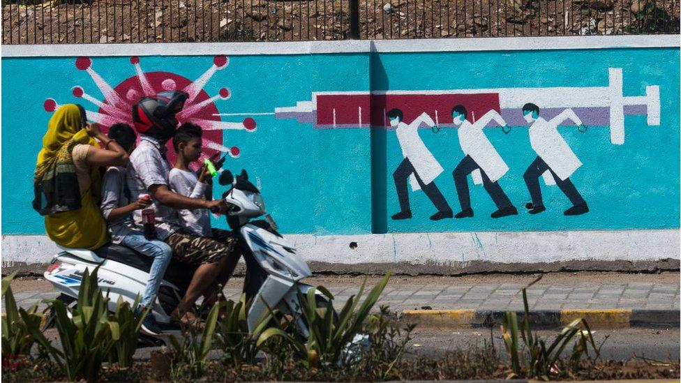 4 personas pasan en moto junto a un mural con personal sanitario embistiendo con una jeringuilla al coronavirus.