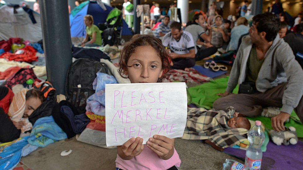 Rebecca de Siria, una niña migrante sostiene un trozo de papel 'Please Merkel Help Me' (Por favor, ayúdame Merkel) mientras su familia espera el transporte a Alemania, en la estación de tren de Budapest Keleti, en 2015.