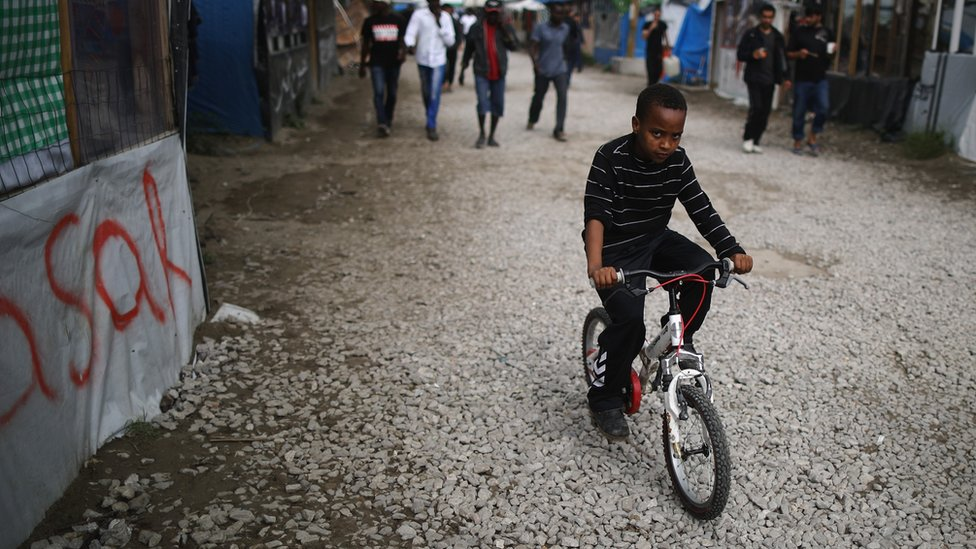 Young boy cycling in the Calais 'Jungle'