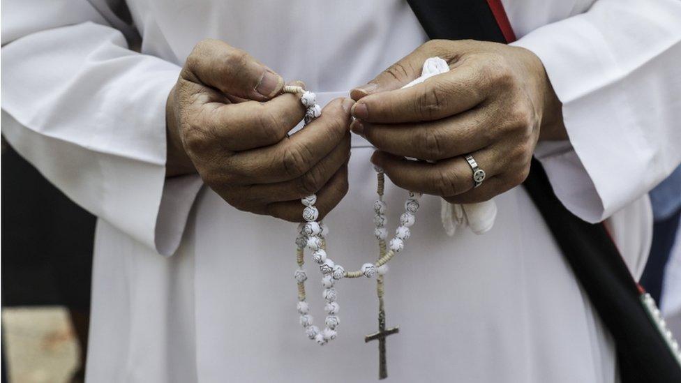 Una persona sosteniendo un rosario.