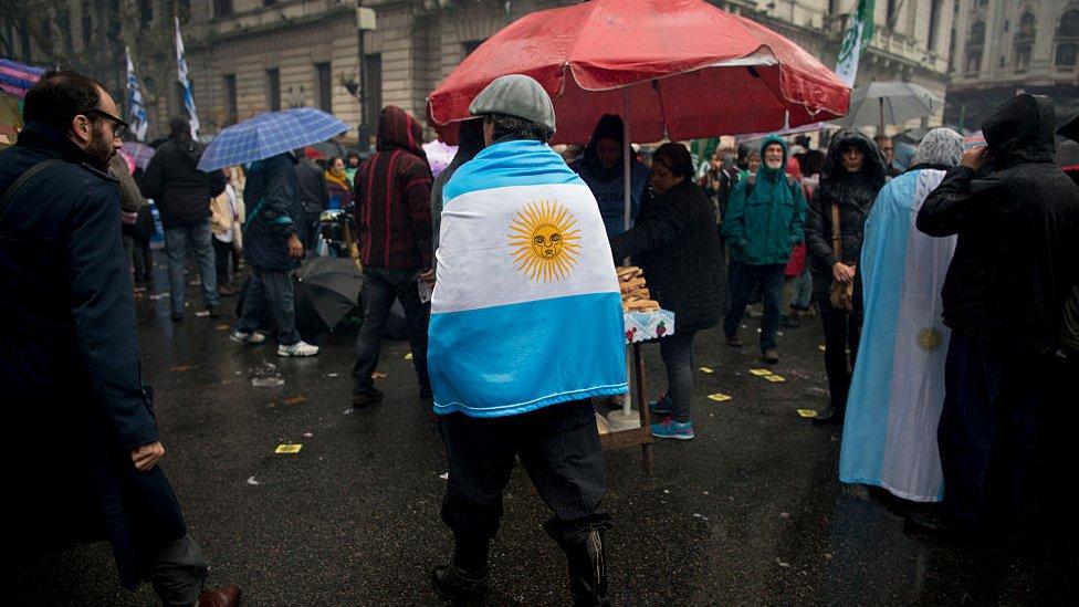 El gobierno insiste en atribuir la suba del dólar al contexto internacional pero sus críticos le achacan que su política de ajuste afecta a la mayoría de los argentinos.