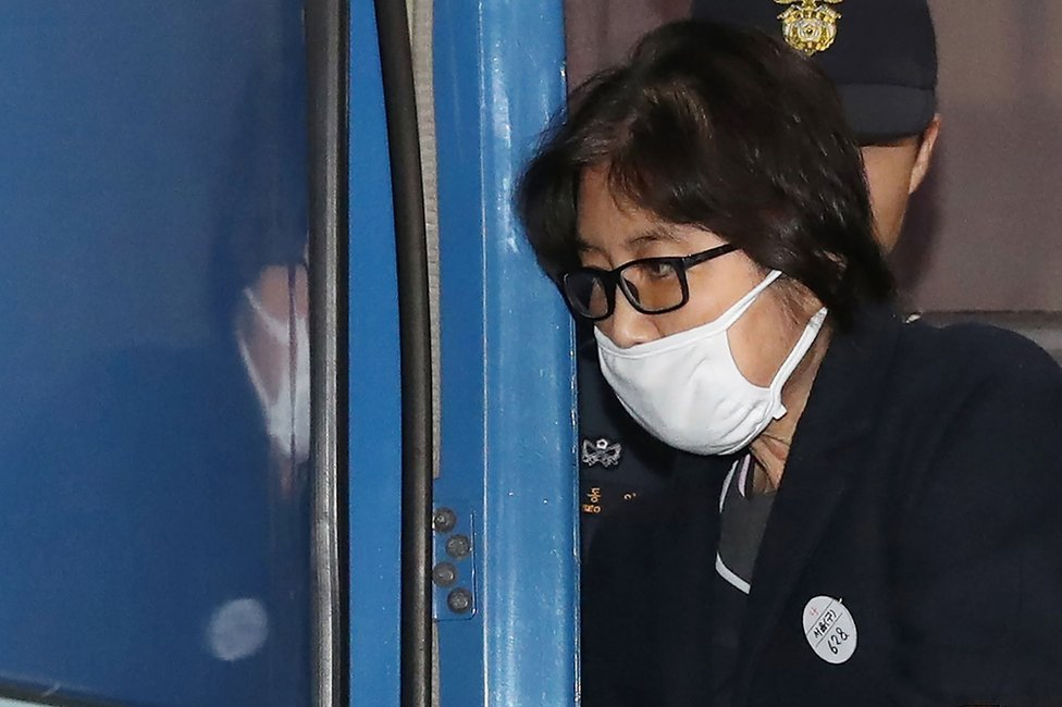 """This picture taken on 19 November 2016 shows Choi Soon-sil, the woman at the heart of a lurid political scandal engulfing South Korea's President Park Geun-Hye, being escorted after questioning at the Seoul Central District Prosecutors"""" Office in Seoul."""