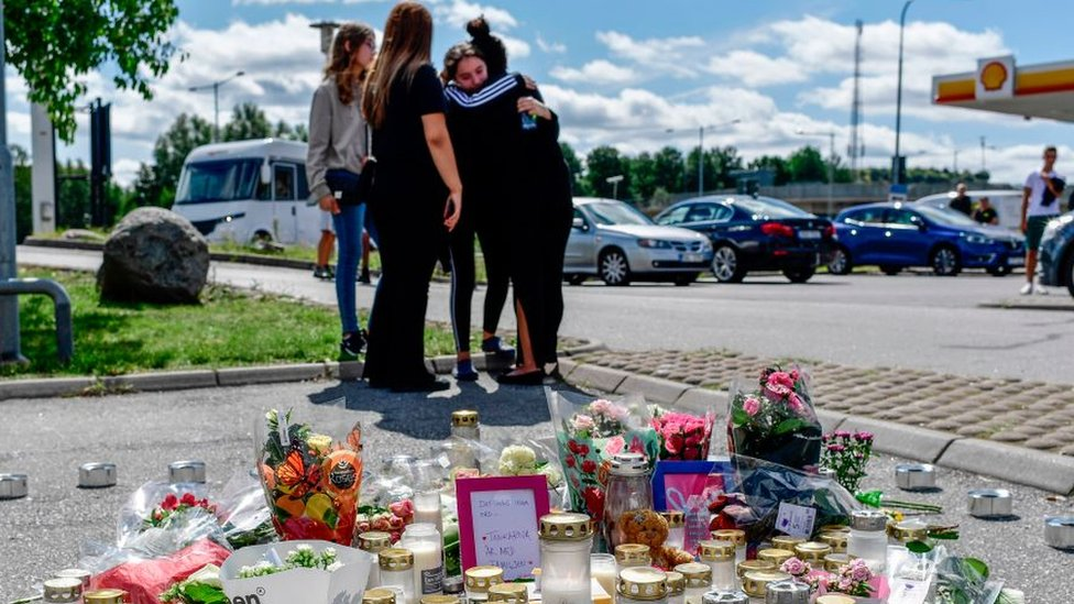 Cuatro niñas se abrazan y se paran junto a un memorial improvisado en el lugar donde una niña de doce años recibió un disparo cerca de una estación de servicio en Botkyrka, al sur de Estocolmo, el 3 de agosto de 2020.