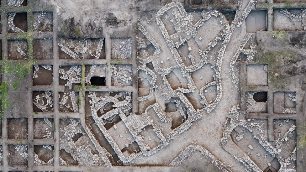 An overhead photo of the excavation site gives a clear view of the planned design of the ancient city.