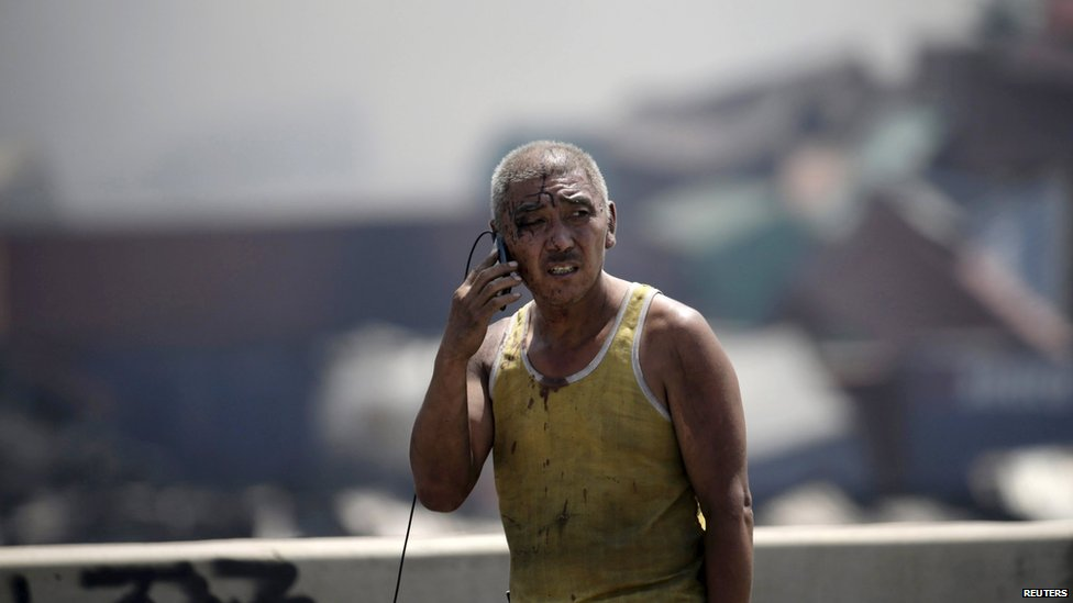 A survivor talk on his mobile phone at the site of the explosions at the Binhai new district in Tianjin August 13, 2015