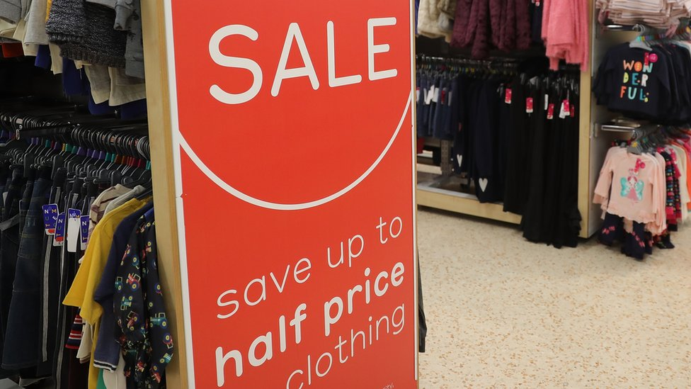 Racks of children's clothes with a big sale sign at one end