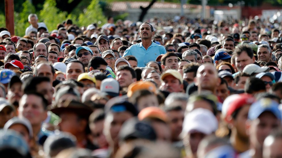 A man peaks over the crowd waiting to cross the border into Colombia from Venezuela on 17 July