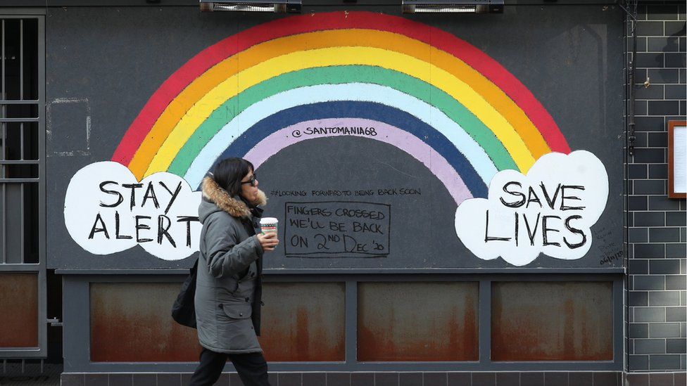 Woman walking past a rainbow mural