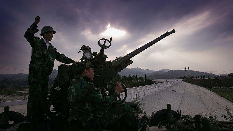 """Un trabajador chino disparando sustancias a las nubes en un intento de """"sembrarlas"""" para que caigan más precipitaciones."""
