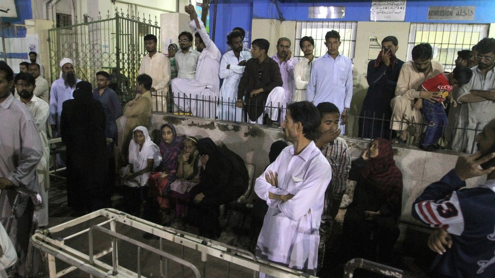 People gather outside an emergency ward of a Karachi hospital after hearing news of a bomb blast at a Sufi shrine, in Karachi, Pakistan