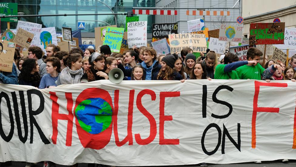 Adolescentes con pancartas exigiendo acciones urgentes contra el cambio climático