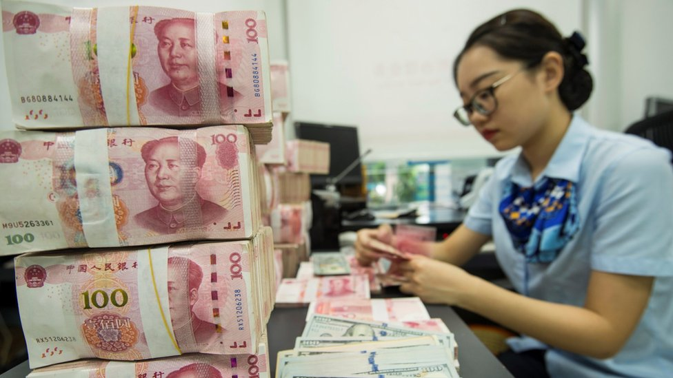 A Chinese bank employee counts 100-yuan notes and US dollar bills at a bank counter in Nantong in China's eastern Jiangsu province on August 28, 2019.