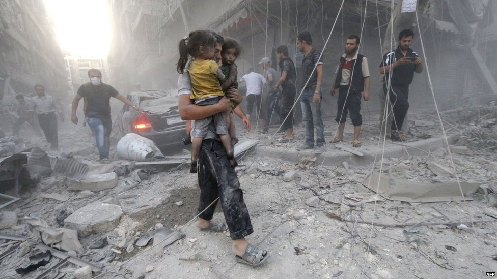 A Syrian man carries two girls covered with dust following a reported air strike by government forces on 9 July 2014 in the northern city of Aleppo.