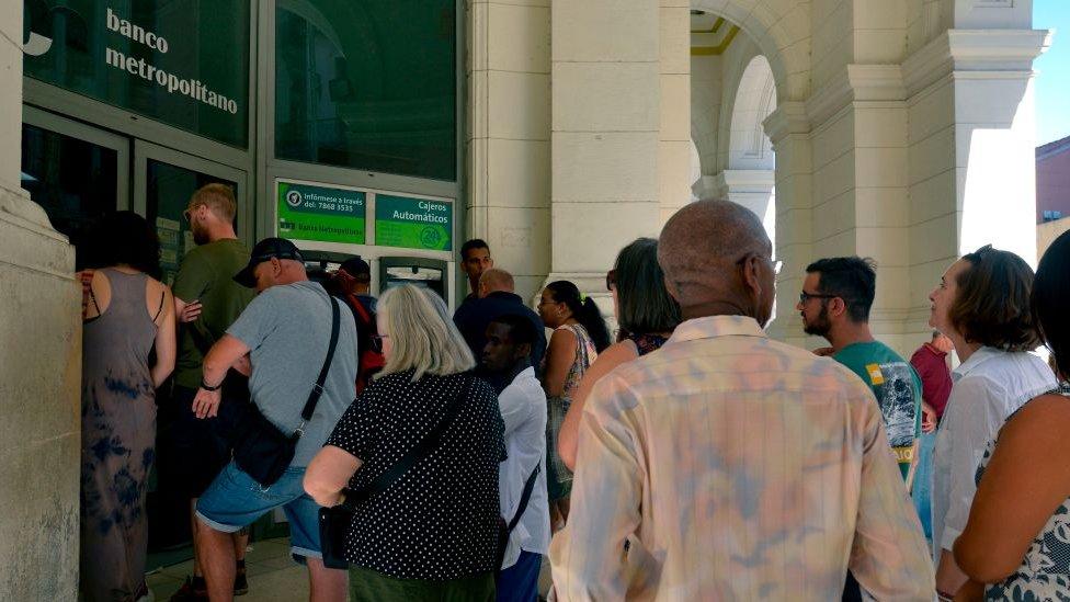 Cubanos y extranjeros en un banco de Cuba
