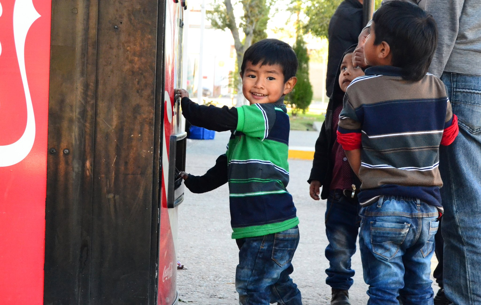 Rogerio's son playing at Coca-Cola machine